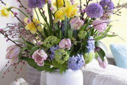 Vårlig bukett med Allium, påskeliljer, tulipaner og blomstrende grener