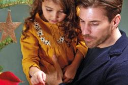 Jente på pappas arm ser på juletreet