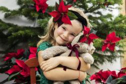 Både jenta og bamsen har pyntet seg med julestjerne på julaften. Forsegl gjerne stilken med blomstertape, så ikke håret blir klissete av plantesaften!